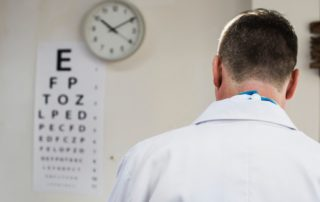 Doctor looking at clock and medical chart